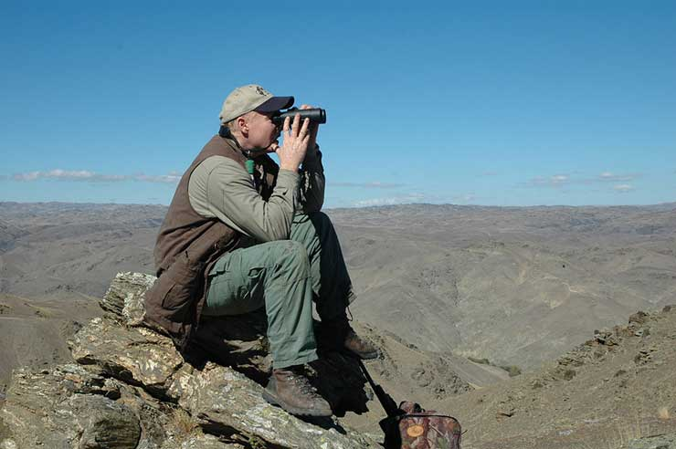 A hunter glassing on top of a hill
